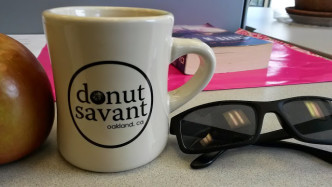 a photo of an apple, a mug reading Donut Savant, and some sunglasses